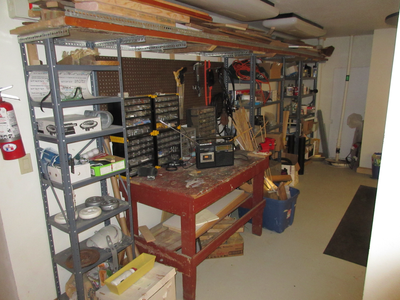 The common workshop with a counter, shelves, and various tools and hardware