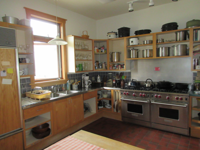 The community kitchen with double industrial ovens, sinks, and many kitchen tools.