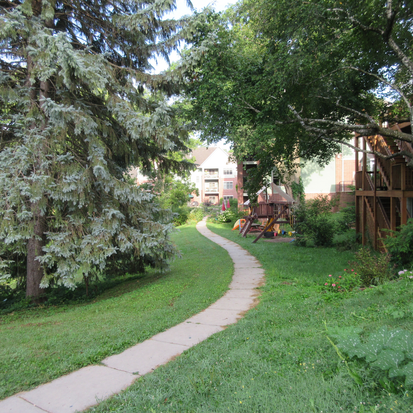 The sidewalk winds its way among trees, gardens, and a play structure.