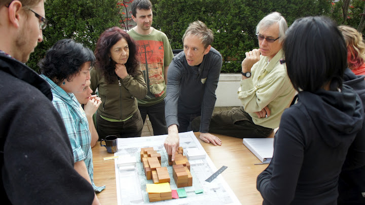 Adults standing around a table on which house-shaped wooden blocks are placed.