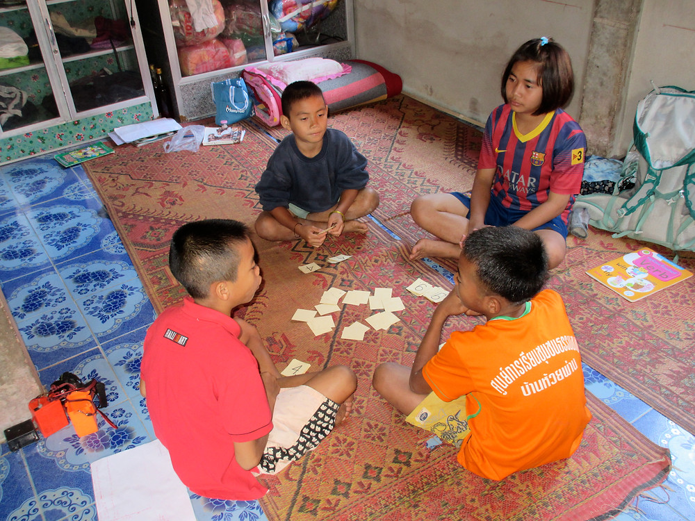 Four children with on a mat playing with handmade cards.