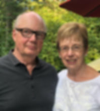 A smiling couple in their early seventies, outdoors in the summer