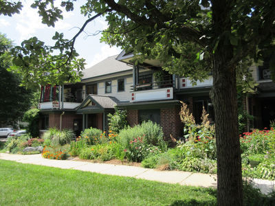Lovely two-storey row housing with lush gardens and a sidewalk in the forefront.