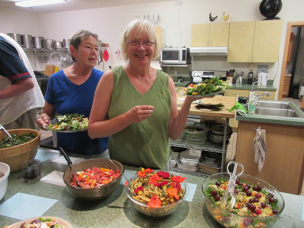 A woman in green at a counter with various salads