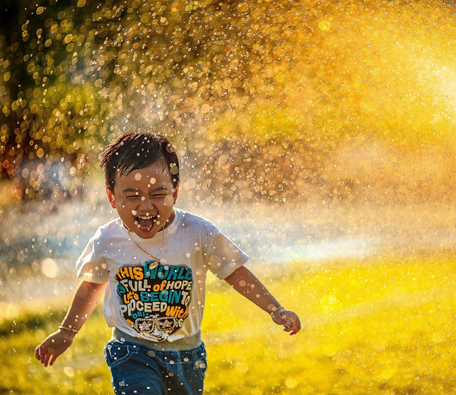 Happy boy playing in the sprinkler
