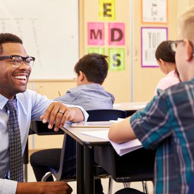 smiling teacher kneeling by desk.jpg