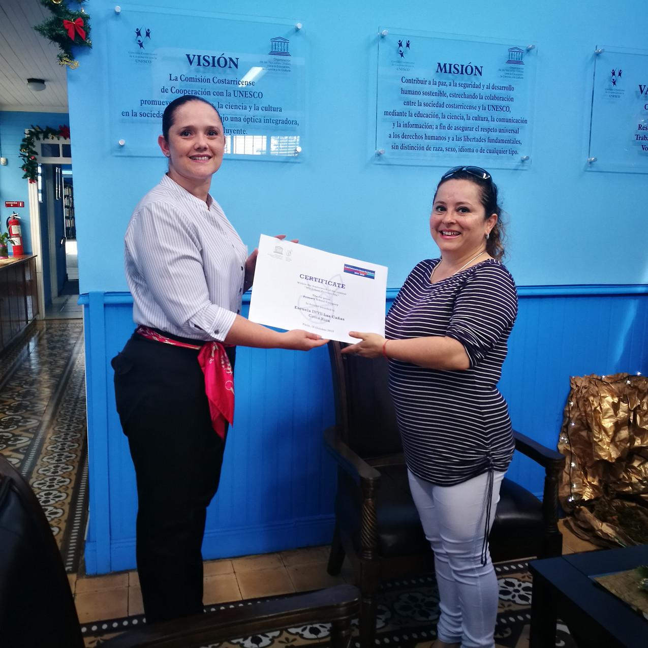 La Sra. Ma. Milagro Arce, docente de grado, recibe el reconocimiento para la Escuela INVU Las Cañas.