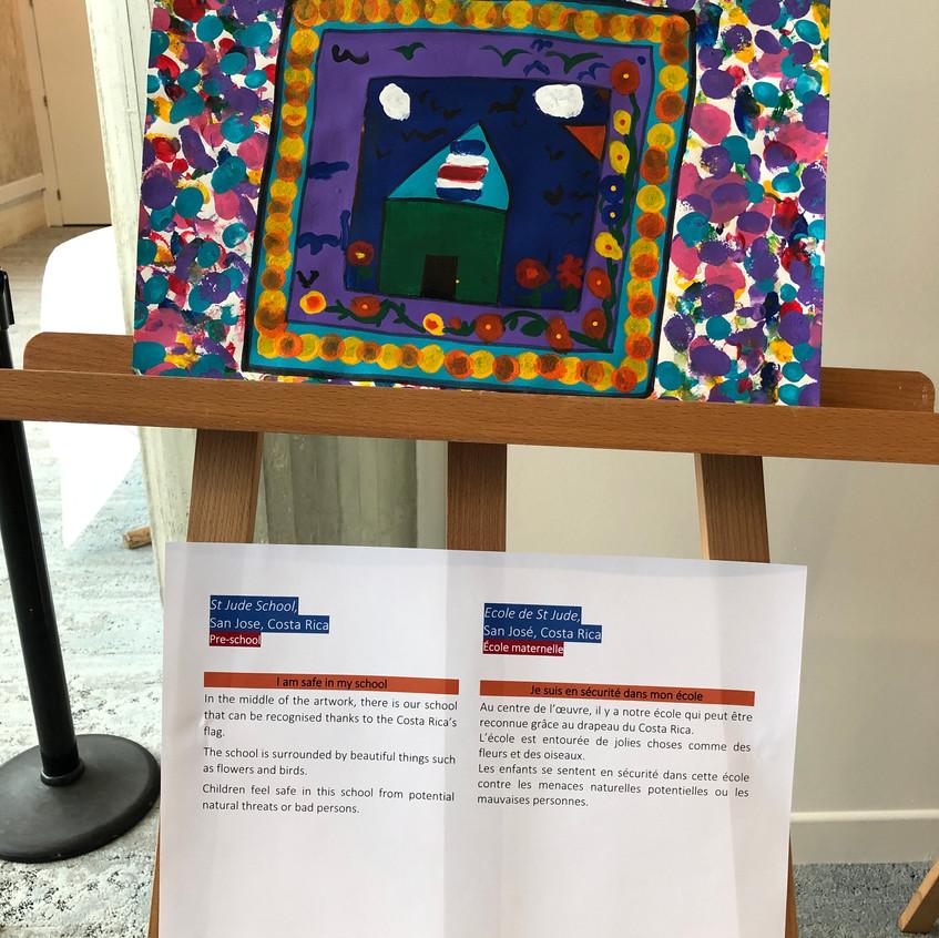 Pintura de estudiantes de educación preescolar de St. Jude School y texto descriptivo, expuestos en la Sede de la UNESCO.