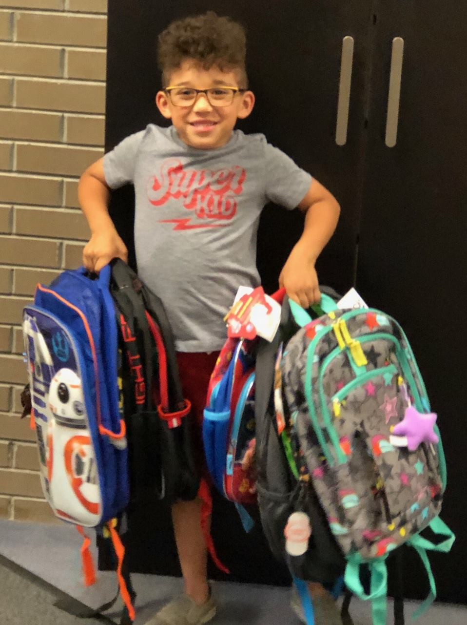 William and the backpacks donated from his birthday party!