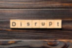 DISRUPT word written on wood block. DISR