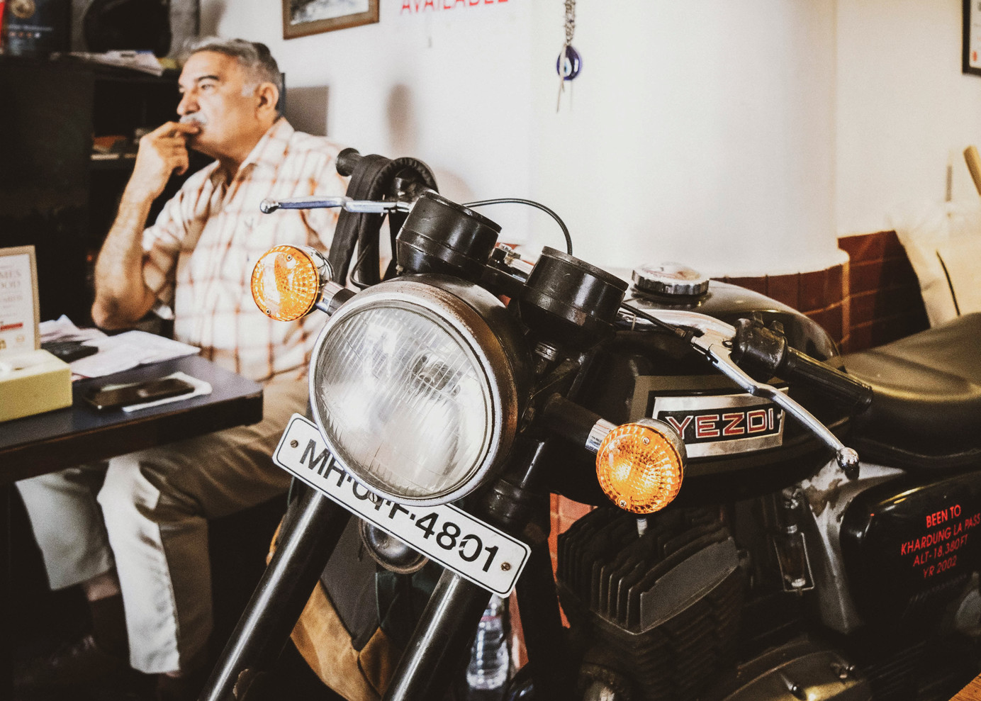 A Yezdi Oilking bike alongside its proud owner, Parvez Patel (seated left), at the heart of Cafe Ideal Corner. Patel had made a trip to Khardung La, the highest motorable road in India, in the year 2002 on this bike. Unfortunately, Yezdi stopped production of their iconic bikes in 1996.