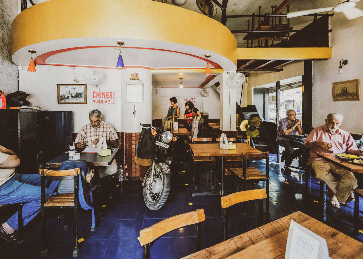 Interiors of Cafe Ideal Corner, named after the Mysore-based motorbike company Ideal Jawa India Pvt Ltd, whose shop was originally located at the very corner where the cafe stands today. The interior is resplendent with royal blue flooring with wooden stairs leading to a loft which is used only if the ground floor is packed with customers.