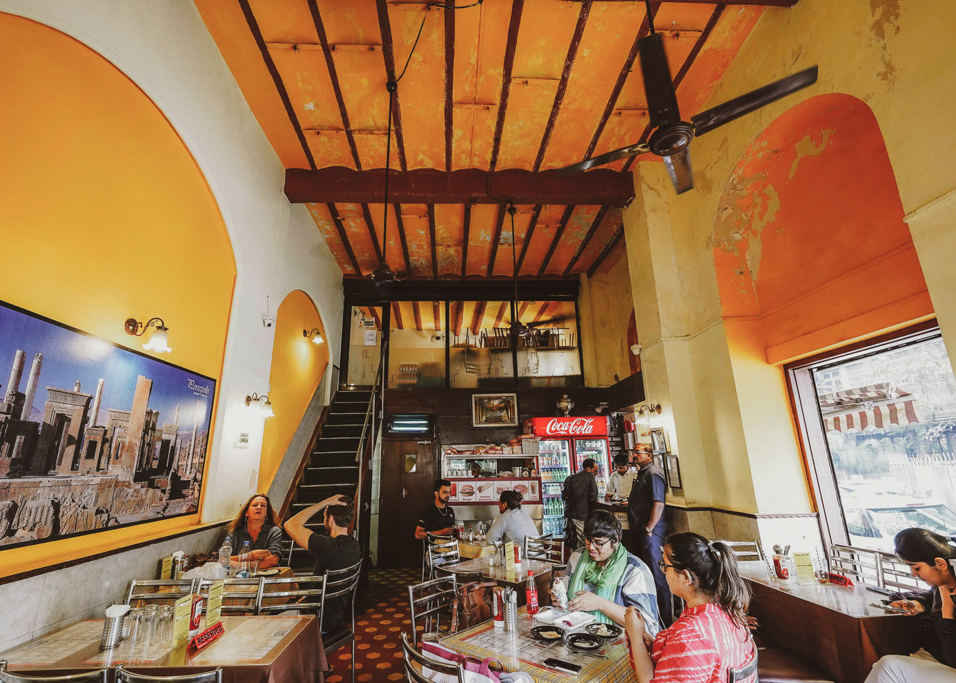 Cafe Piccadilly, with its large French windows and colonial decor, opposite Electric House on Colaba Causeway. The cafe has been in operation since 1957. Customers are greeted by a grand panorama of the ruins of Persepolis, the ancient capital of the Achaemenid Empire located in the Fars province of Iran. The French windows of the cafe offer a view of the street life, which the customers can enjoy along with their favourite shawarmas.