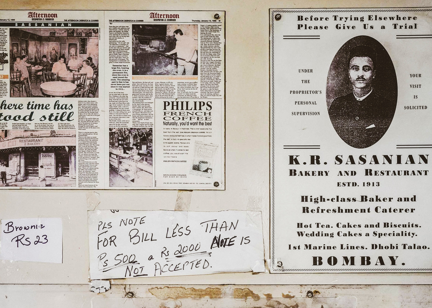 The advertisement leaflet on the right was distributed when Sassanian Boulangerie was established in 1913 as K.R. Sasanian. They served hot tea, cakes and biscuits. Wedding cakes were a speciality, popular with the European, Anglo-Indian, Parsi and Indian Christian communities living in South Bombay. The news clipping on the left, titled 'Where Time has Stood Still', reminiscence about the competition between Sassanian and Bastani, another legendary Irani restaurant at Dhobi Talao, famous for its chicken pattice. Unfortunately, Bastani has long since closed down.