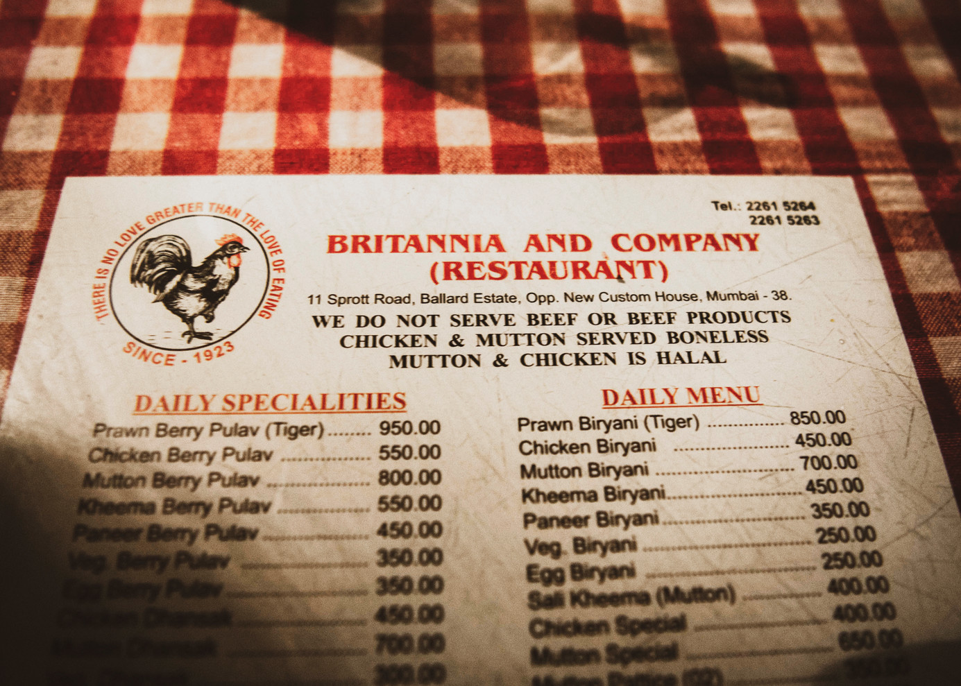 Tucked between the chequered table cloth and glass panes, the menu card of Britannia & Co. The food items are inclusive, keeping in mind the wide range of customers in a multicultural city such as Mumbai and their diverse eating habits. For example, Britannia's menu makes it clear that they do not serve beef or beef products and all of their meat is halal.