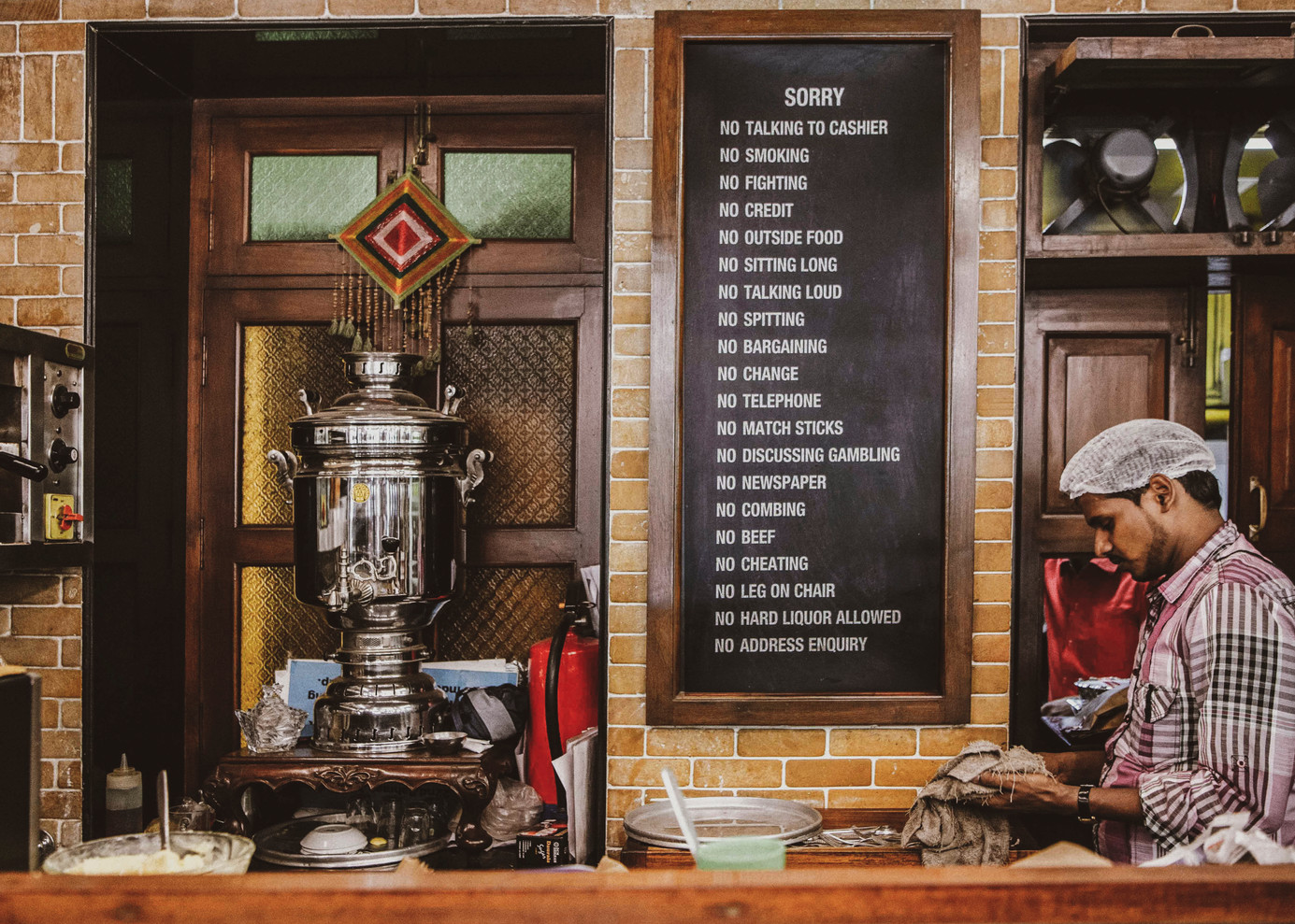 A typical blackboard with a list of rules at Cafe Irani Chaii of Mahim. A quirky feature at the Irani cafes are the long list of 'restaurant rules' which are expected to be followed by all including the owners and staff. Irani Chaii's 'no combing' rule seems out of place even on a list of oddities.