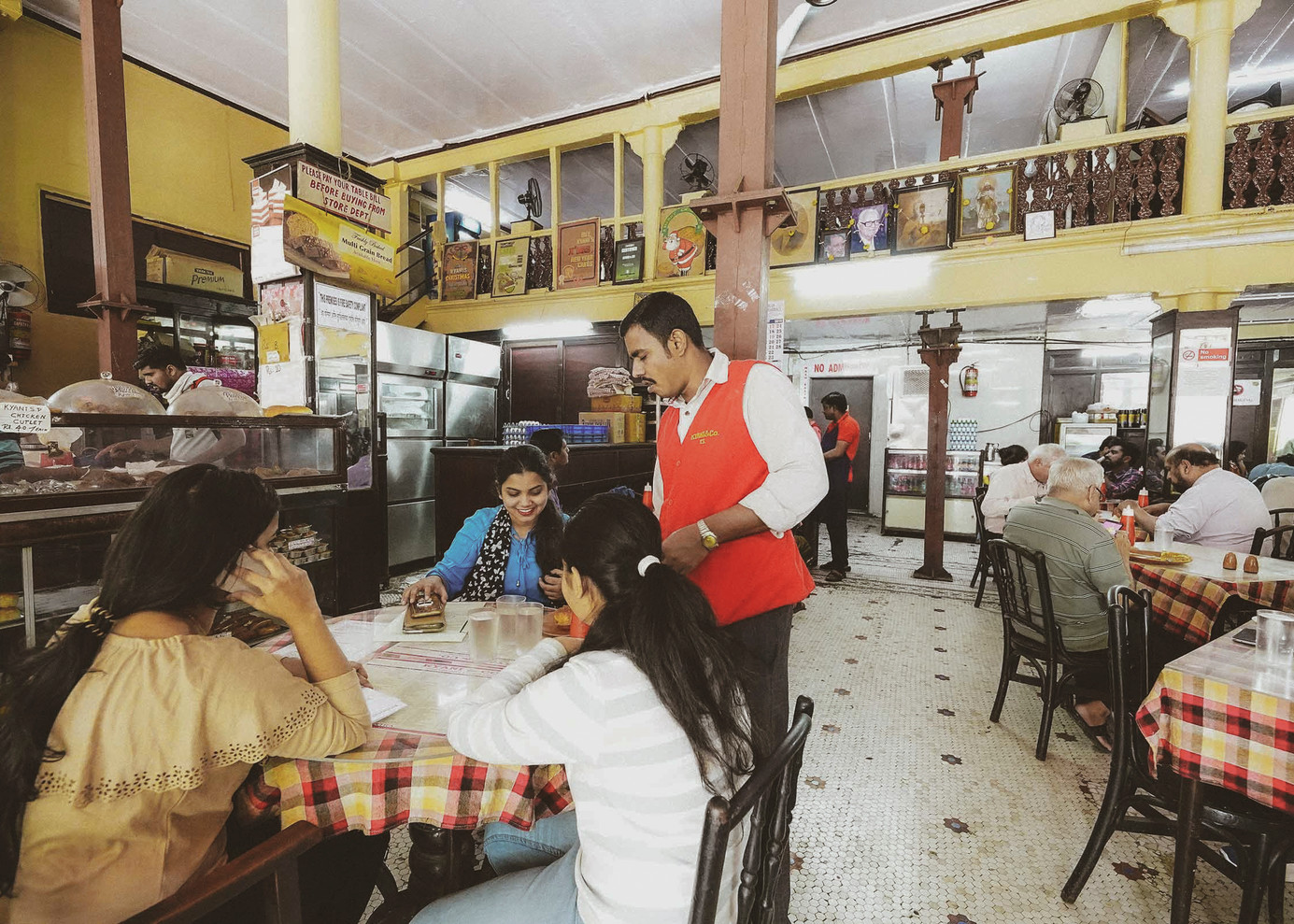 A waiter taking orders from enthusiastic customers at Kyani and Co. The eatery was established in 1904, which makes it the oldest surviving Irani cafe in Mumbai; it is now listed as a heritage monument. Kyani is known for the period ambience, showcasing high ceilings with colonial-style fans, tiled floors and Italian-marble-topped tables. The tables are complemented with vintage bentwood or bent-cane chairs.