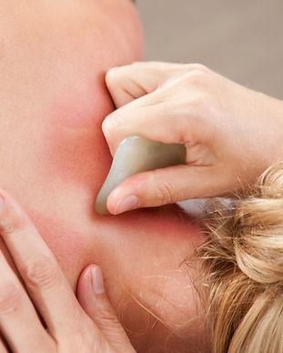 Female receiving gua sha treatment to ne