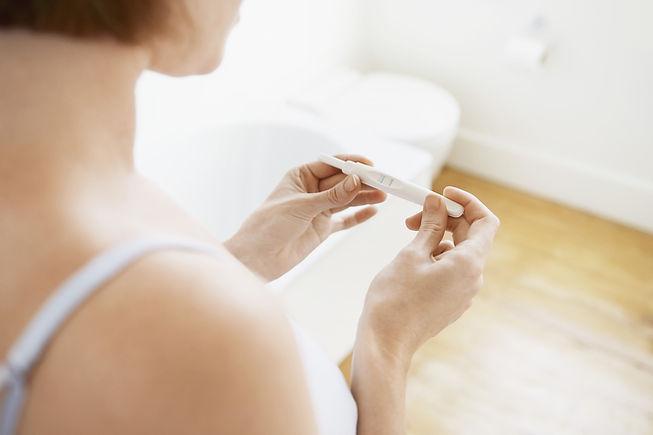 Young woman checking pregnancy test kit