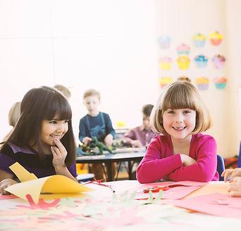 초등학교 수업 시간에 테이블에 앉아 웃는 여자