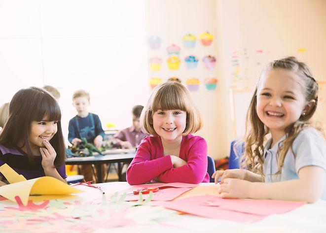 Souriant jeunes filles assis à table en