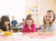 Smiling girls sitting at table in elemen