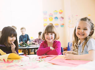 Smiling girls sitting at table in elementary class