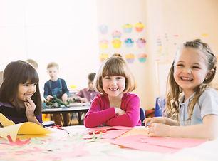 Uśmiechnięte dziewczyny siedzą przy stole w klasie podstawowej