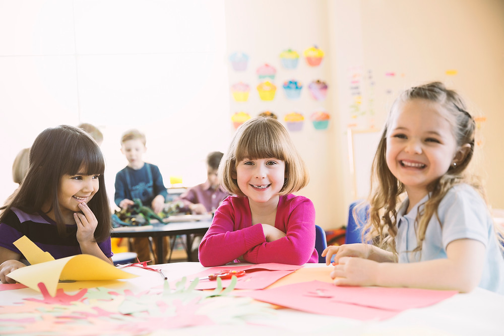 Three girls are sitting at a table in a classroom. There are craft supplies strewn about on the table, and all three girls are looking at the camera.