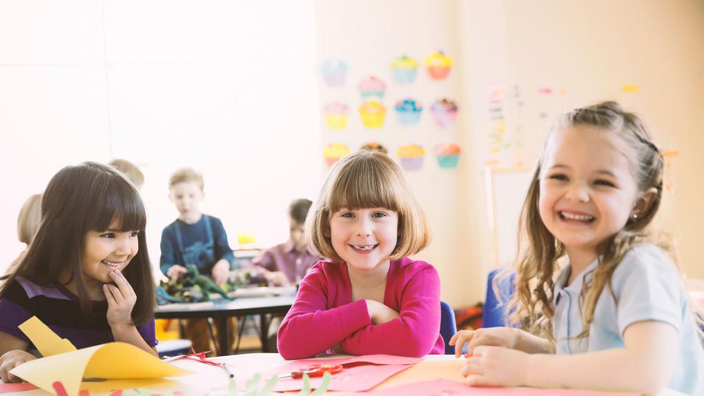 Lächelnde Mädchen am Tisch in der Grundk