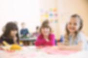 Улыбающиеся девушки, сидя за столом в эл