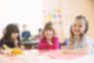meninas sorrindo sentado à mesa na class