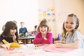 Uśmiechnięte dziewczyny siedzą przy stol