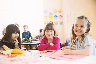Souriant jeunes filles assis à table en classe élémentaire