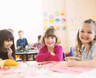 Lachende meisjes zitten aan tafel in de lagere klasse