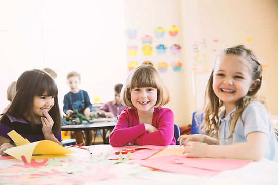 基本クラスでテーブルに座って笑顔の女の子