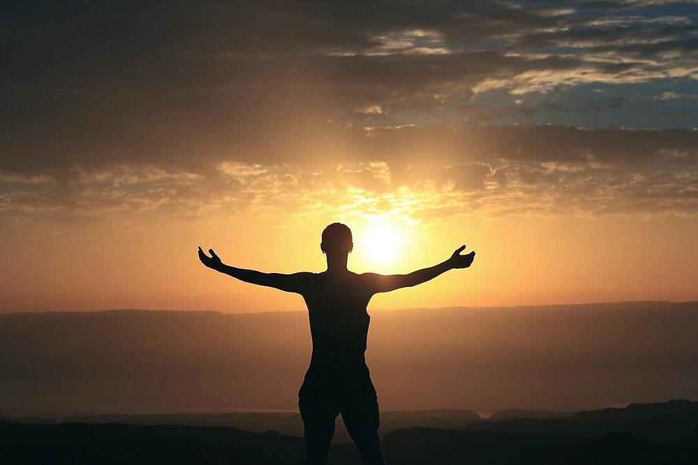 Ocean sunrise open arms silhouette showing gratitude