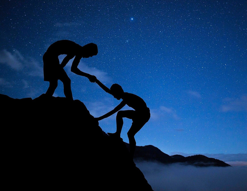 Silhouette of person helping up another person up a mountain with a stary night background