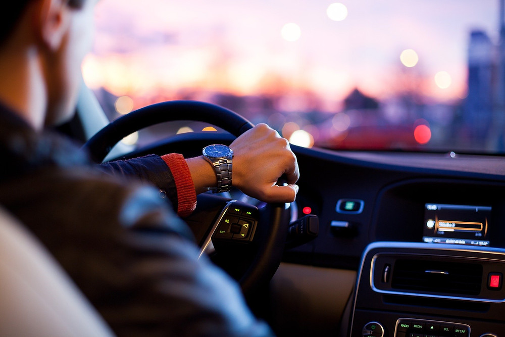 Man driving car with focus on steering wheel