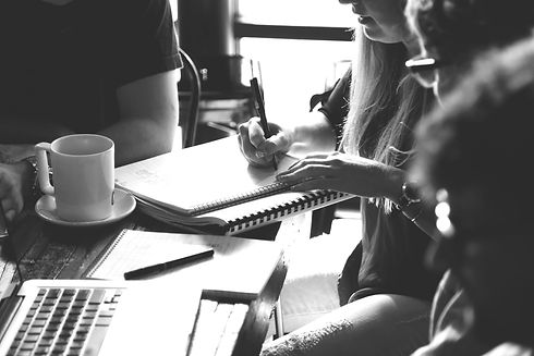 Taking notes with coffee during informal meeting black and white