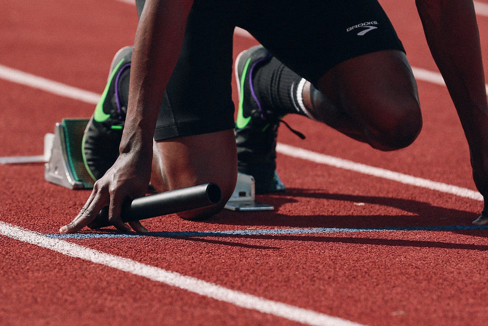 runners legs on starting block with a relay