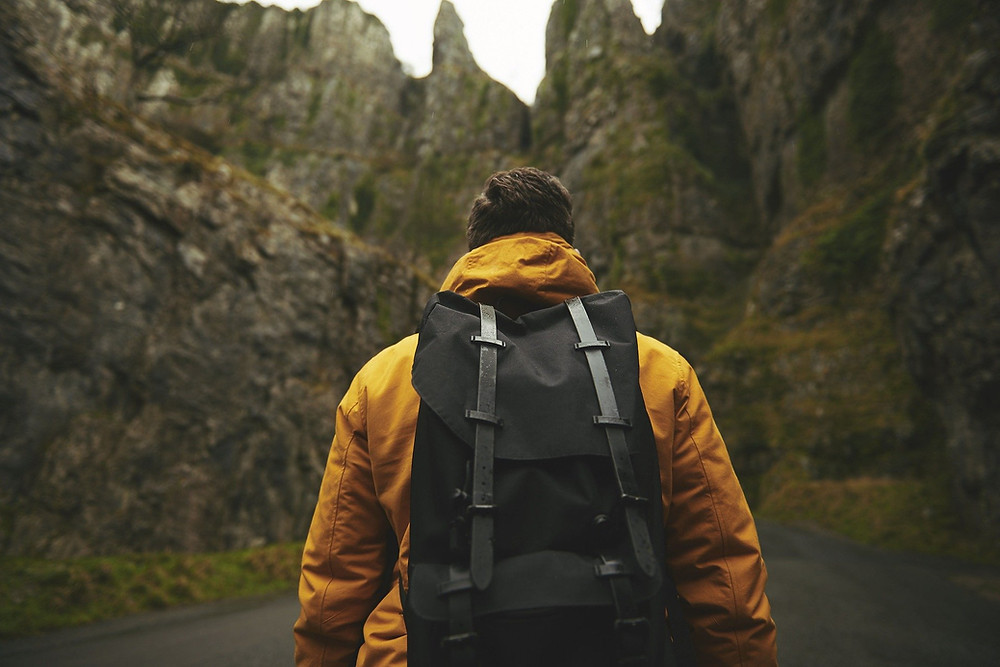 Adventurous man with yellow jacket, black bag looking at mountains doing something different