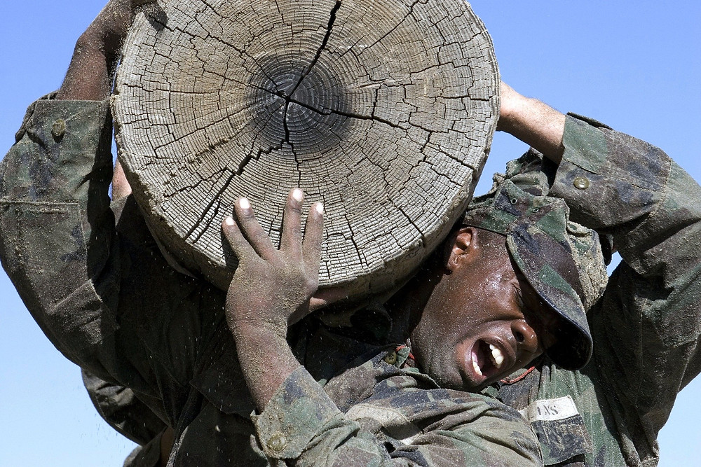 Soldier struggling to carry large log showing persistance