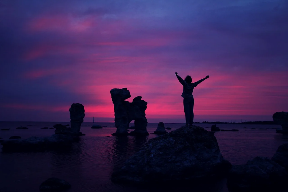 Silhouette of woman stretching at beach during purple sunset