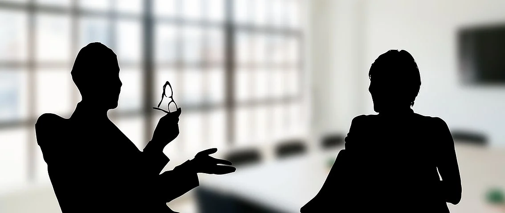 Silhouette of man holding glasses coaching another person during a meeting