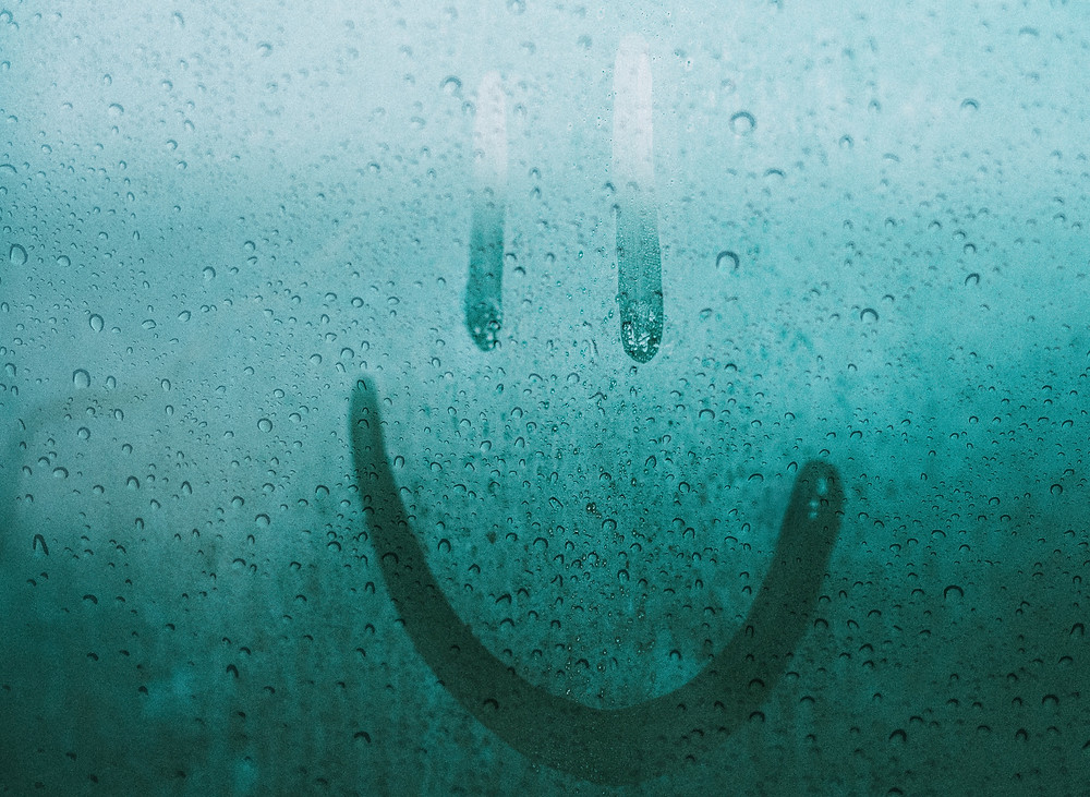 Rainy window with smile drawn in condesation