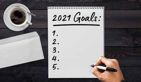 Notepad with 2021 goals being written next to coffee