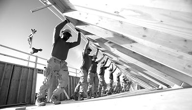Construction workers lifting wall showing positive teamwork