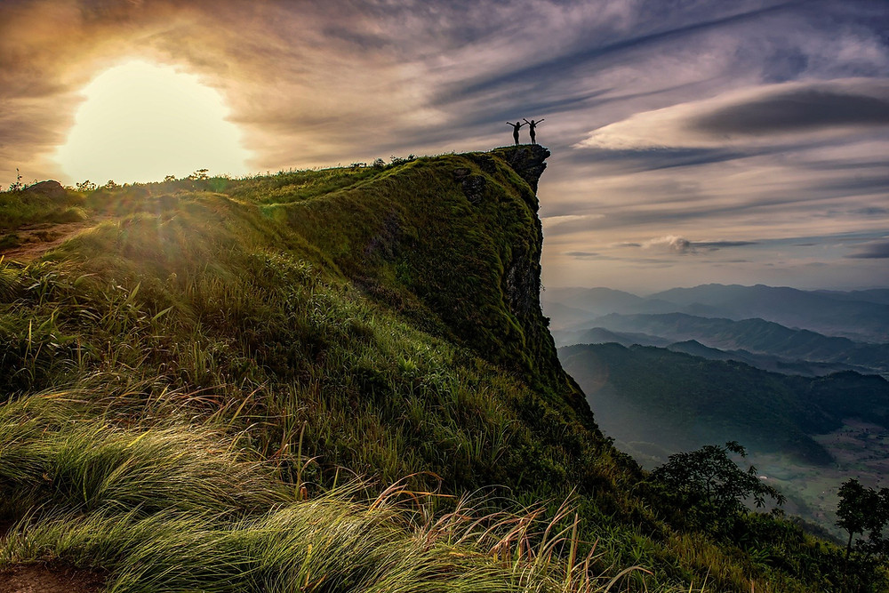 Sun rising above cliff with 2 people having their arms outstretched