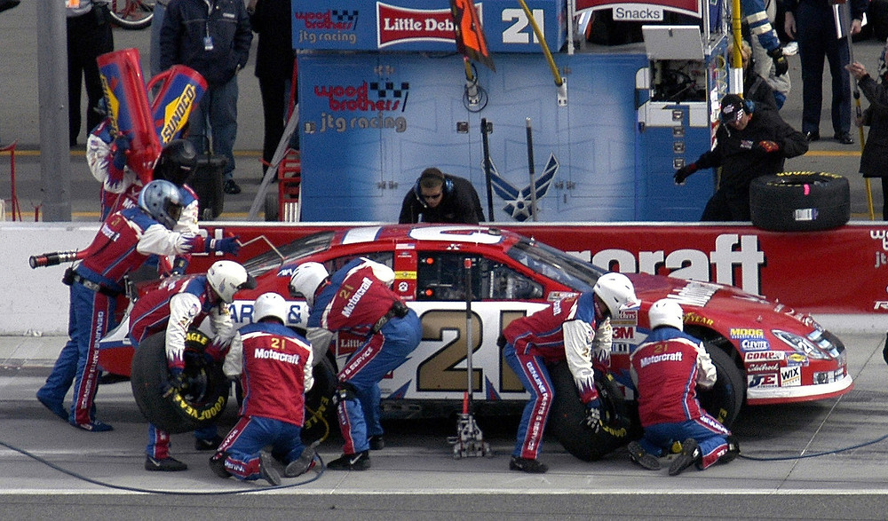 Motorcraft pit crew changing tires of a NASCAR vehicle